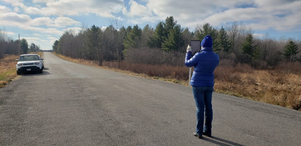 Genevieve takes a photograph of the road near a culvert site