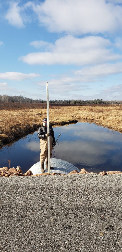 Jon stands on a culvert pipe holding a measuring stick