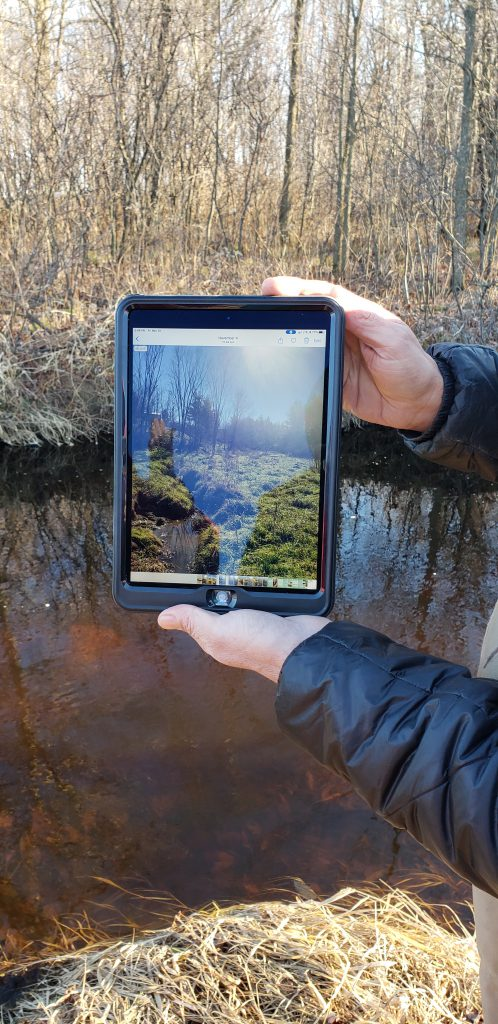 a man holding a tablet with a photo of a culvert site
