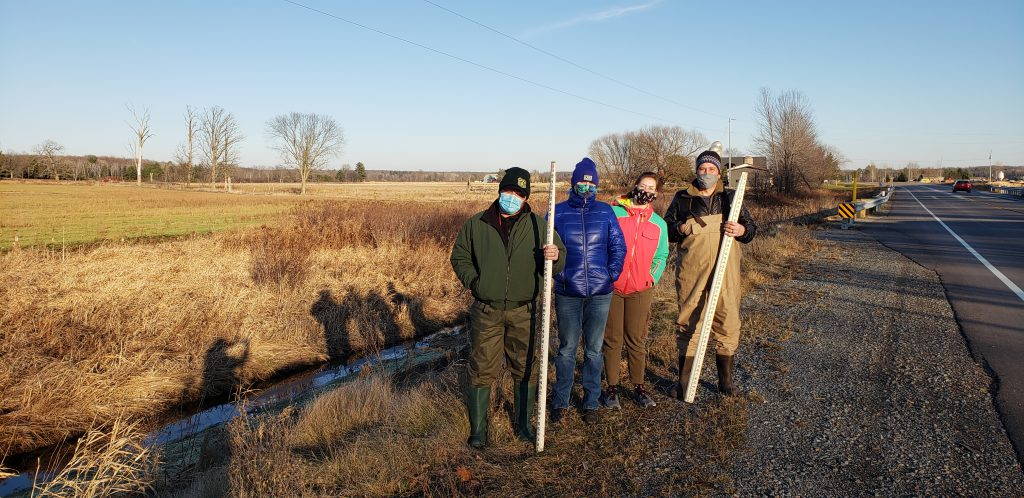 a group of people wearing masks and standing near a culvert site