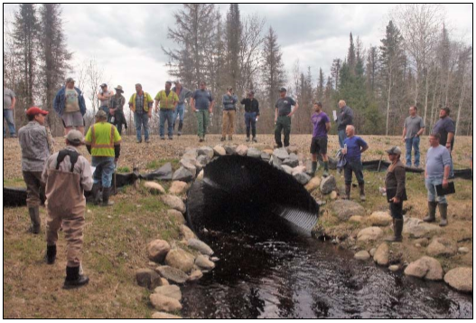 several people standing around a large culvert